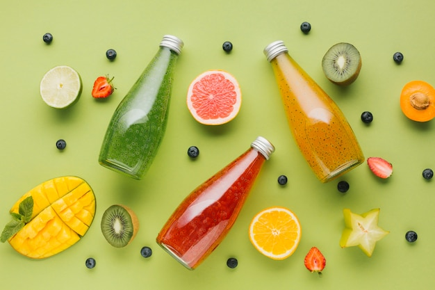 Fatias de frutas planas e garrafas de suco
