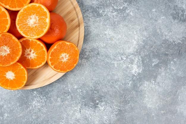 Fatias de frutas suculentas de laranja frescas em uma placa de madeira.