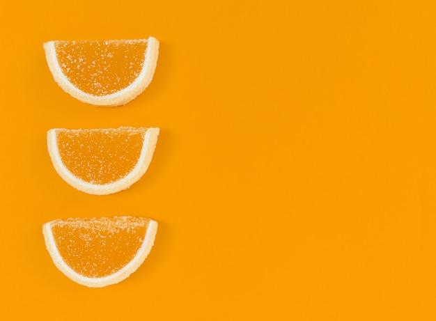 Fatias de geléia de laranja com açúcar em um fundo de cor laranja com espaço de cópia.