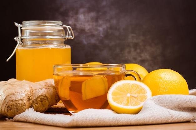 Fatias de gengibre e limão em um prato, jarra com mel e xícara de chá com limão em uma mesa de madeira