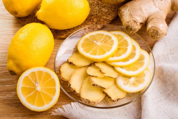 Fatias de gengibre e limão em um prato sobre uma mesa de madeira