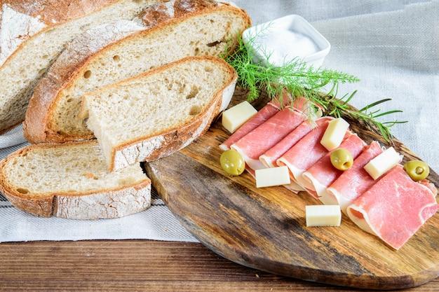 Fatias de jamon, integral de pão, azeitonas e queijo numa tábua de madeira.