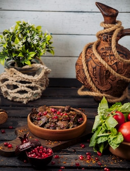 Fatias de kebab de cordeiro, guarnecidas com romã e ervas em panela de barro