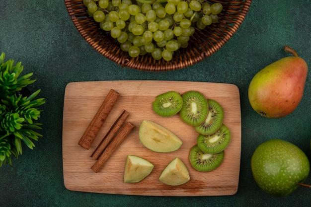 Fatias de kiwi com canela em um suporte com maçã verde, pêra e uvas em um fundo verde.