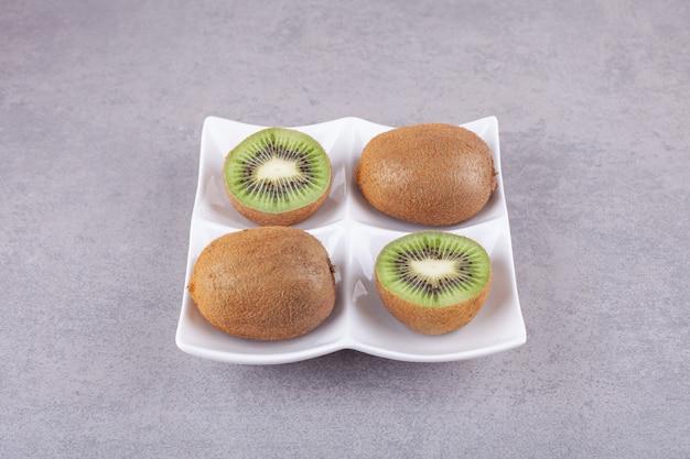 Fatias de kiwi delicioso com folhas colocadas em um prato verde.