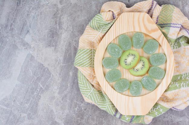 Fatias de kiwi e doces de geleia na placa de madeira.