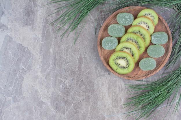 Fatias de kiwi e geleias na placa de madeira com o ramo.