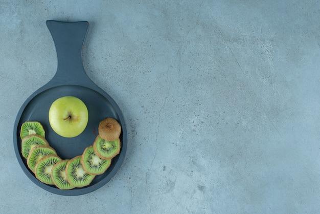 Fatias de kiwi e maçã em uma panela, no fundo de mármore. foto de alta qualidade