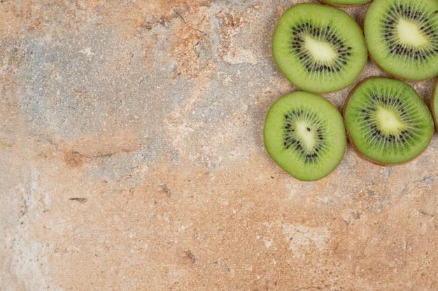 Fatias de kiwi fresco em bakground de mármore.