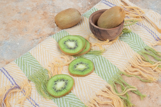 Fatias de kiwi fresco na toalha de mesa colorida.