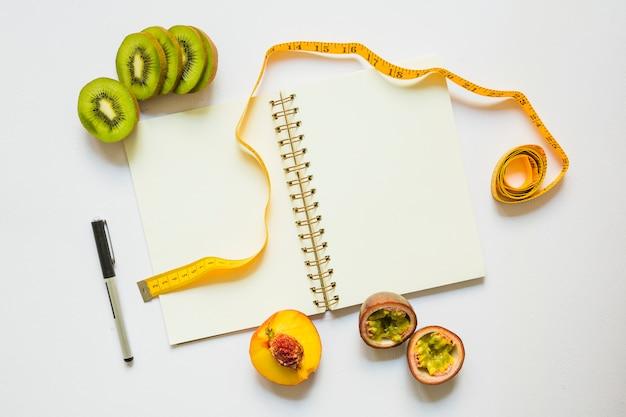 Fatias de kiwi; pêssego e maracujá com fita métrica; caneta e caderno espiral