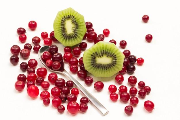 Fatias de kiwi verde e cranberries vermelhos na colher. postura plana