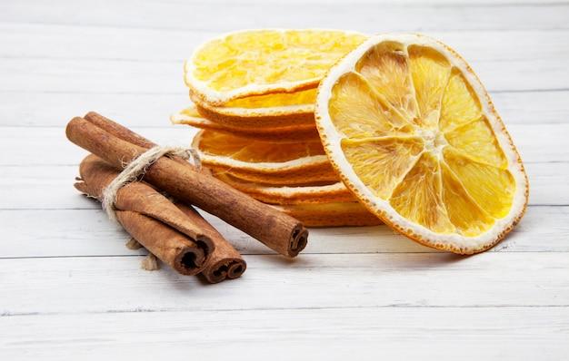 Fatias de laranja com canela sobre um fundo claro de madeira, apreciando as especiarias