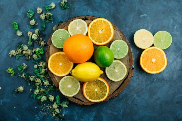 Fatias de laranja com limão, limão, flores secas planas leigos na placa azul e de madeira suja
