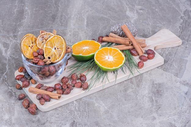 Fatias de laranja com quadris secos e paus de canela em uma travessa de madeira