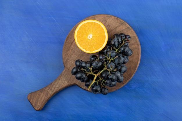 Fatias de laranja com uvas na tábua de madeira