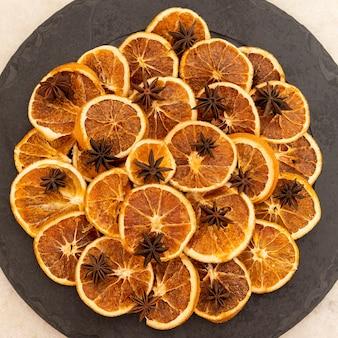 Fatias de laranja desidratada e anis estrelado em pedra preta. foco seletivo.