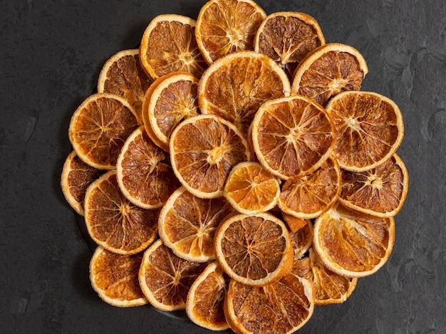 Fatias de laranja desidratada em pedra preta. foco seletivo.