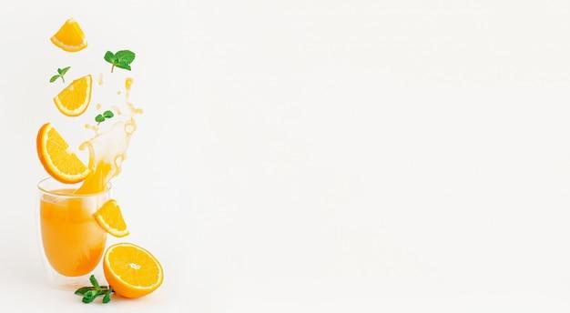 Fatias de laranja e hortelã voando sobre o copo de espirrar suco fresco. conceito de estilo de vida saudável.