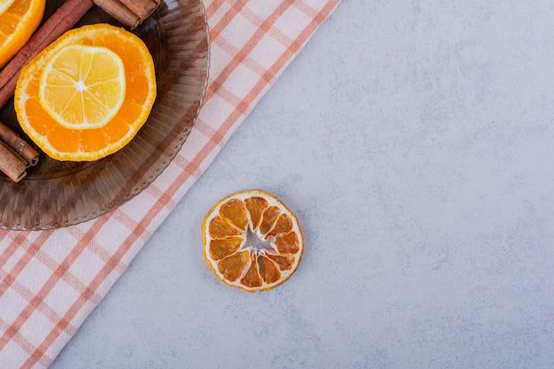 Fatias de laranja e limão em uma tigela de vidro com paus de canela.