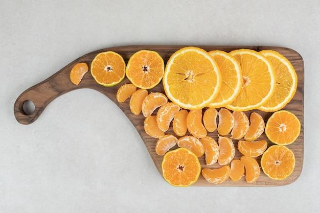 Fatias de laranja e tangerina na placa de madeira