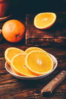 Fatias de laranja em prato branco em ambiente rústico