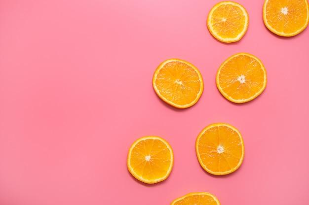 Fatias de laranja em um fundo rosa. padrão de frutas frescas fatias de laranja em fundo rosa