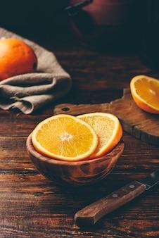 Fatias de laranja em uma tigela de madeira rústica