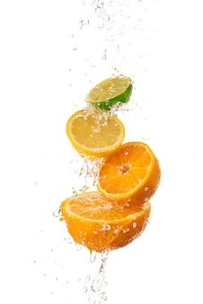 Fatias de laranja, limão e kiwi uma em cima da outra e água corrente por cima.