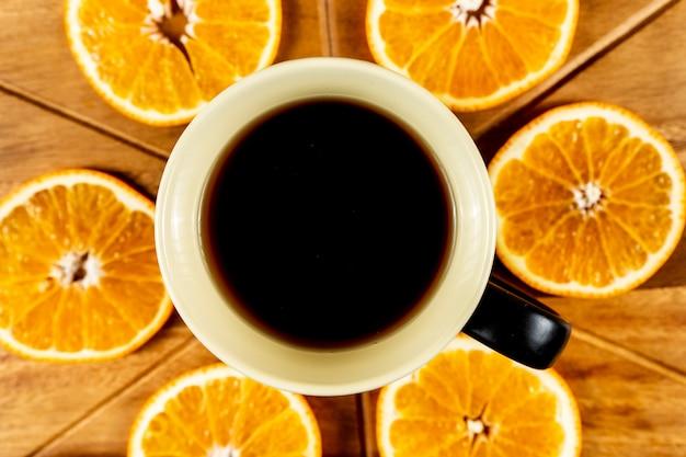 Fatias de laranja na tábua de madeira e uma caneca de café