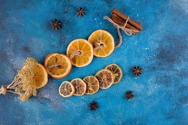 Fatias de laranja seca com paus de canela na mesa azul.
