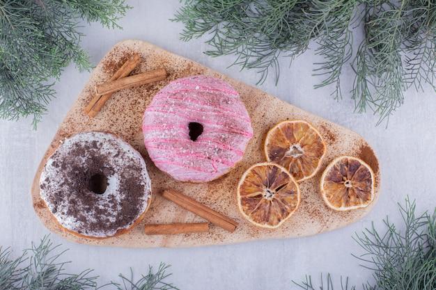 Fatias de laranja secas, donuts e paus de canela em uma placa sobre fundo branco.