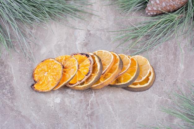 Fatias de laranja secas em caldo na superfície de mármore