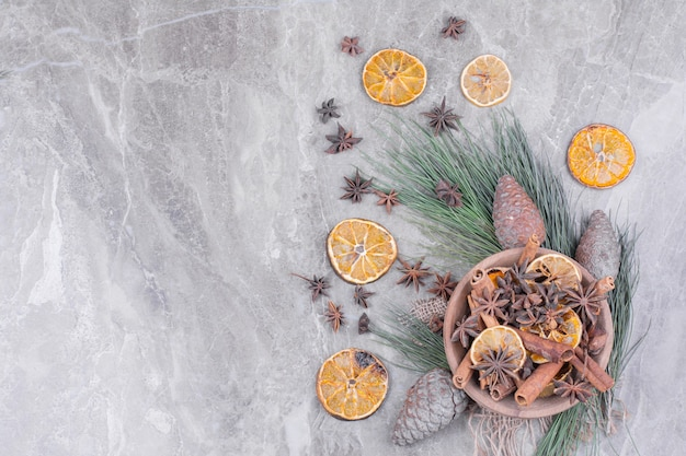 Fatias de laranja secas, paus de canela e flores de anis em um copo de madeira