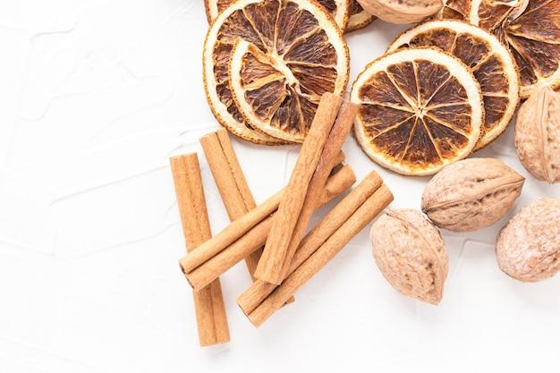 Fatias de laranja secas, paus de canela e nozes. especiarias de natal. tema de ano novo. foco seletivo.
