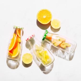 Fatias de laranja suculenta e garrafas de vidro com frutas cítricas cortadas
