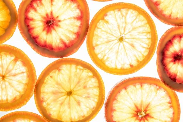 Fatias de laranja vermelhas brilhantes em branco