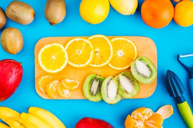 Fatias de laranjas e kiwi na tábua de cortar rodeado de frutas em fundo azul