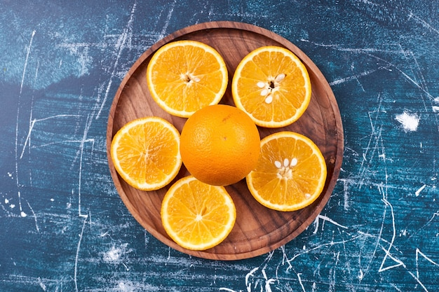 Fatias de laranjas e tangerinas em uma travessa de madeira, vista superior