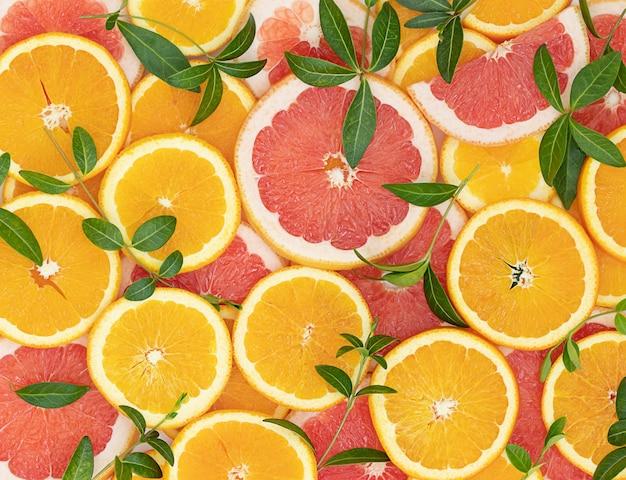 Fatias de laranjas e toranjas e folhas verdes