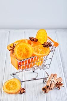 Fatias de laranjas secas ou tangerinas com anis e canela em um carrinho de supermercado vegetarianismo e alimentação saudável.