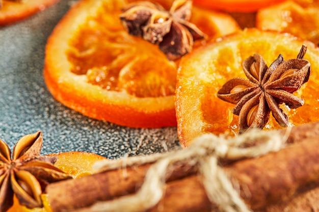 Fatias de laranjas secas ou tangerinas com anis e canela, em uma parede azul. vegetarianismo e alimentação saudável.
