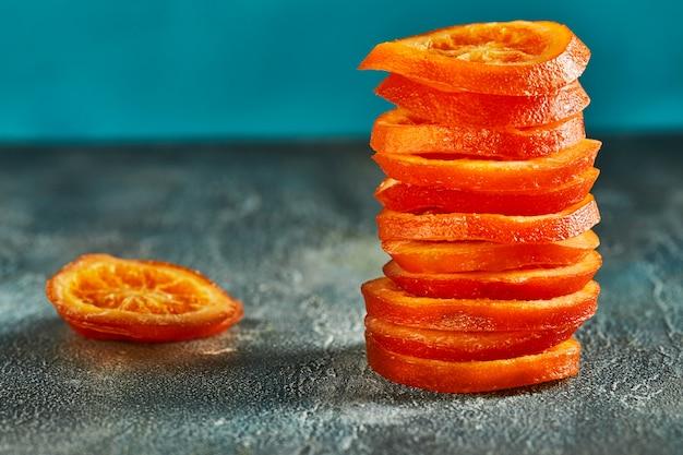 Fatias de laranjas secas ou tangerinas em uma parede azul. vegetarianismo e alimentação saudável. copie o espaço
