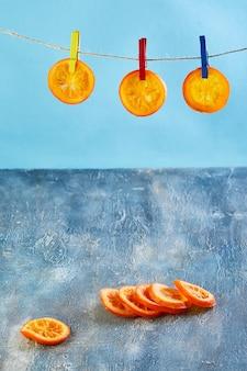 Fatias de laranjas secas ou tangerinas são penduradas no varal com prendedores de roupa na parede azul. vegetarianismo e alimentação saudável. copie o espaço