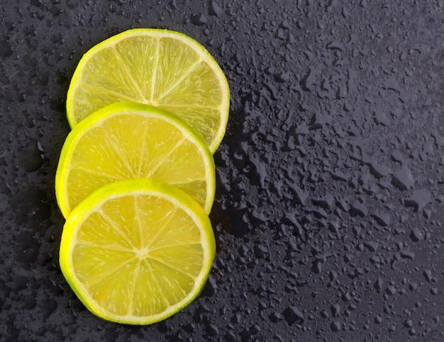 Fatias de lima frescas com gotas de água no preto