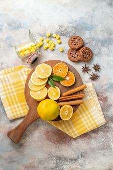 Fatias de limão, canela e limão em uma tábua de madeira e biscoitos na mesa branca