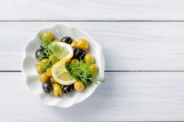 Fatias de limão com azeitonas e endro na mesa de madeira branca