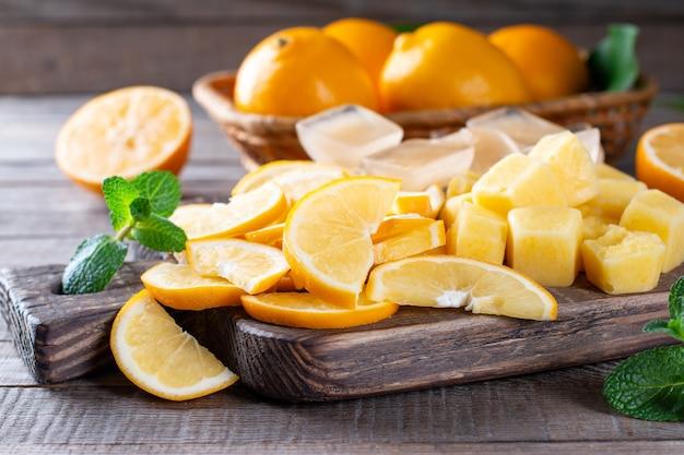 Fatias de limão congeladas e cubos de suco de limão em uma placa de corte sobre uma mesa de madeira, frutas congeladas