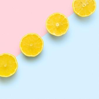 Fatias de limão em linha sobre fundo rosa e azul pastel.