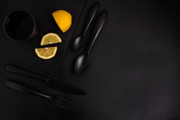 Fatias de limão em um fundo preto com talheres preto, um copo preto e uma placa preta, vista superior